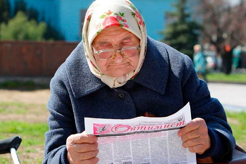 Бабушка читает газету оптимист